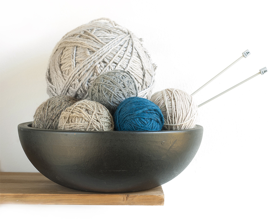 large and small size balls of wool in ceramic bowl